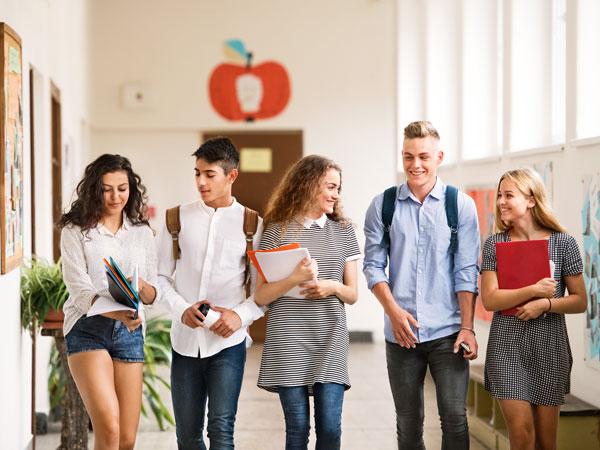 Gut gelaunte Schüler verlassen die Schule