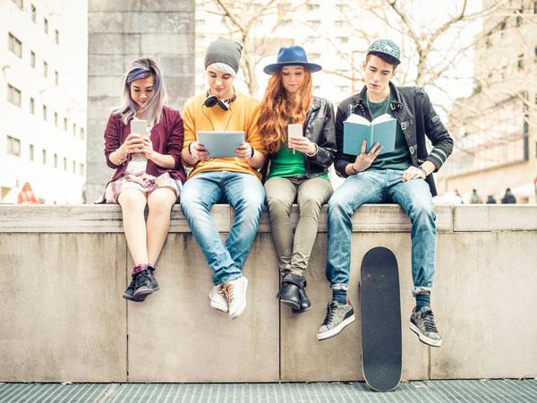 Mehrere junge Menschen lesen Infos für ihre weitere Ausbildung